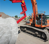 Red MGF Concrete Pipe Culvert Equipment in use at a construction site picking up a concrete pipe