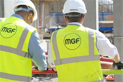 Two men wearing hard hats and yellow MGF High Vis vests overlooking a work site
