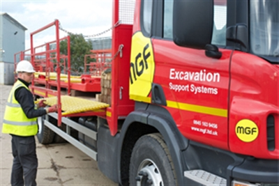 Site worker wearing protection gear unloading a red MGF truck with the words 'Excavation Support Systems' on the side
