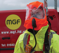 Man fitted with full body safety equipment and breathing apparatus in front of a red MGF branded van