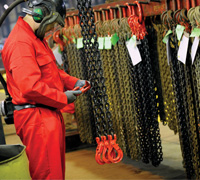 Worker in overalls and breathing mask inspecting MGF chains inside a warehouse