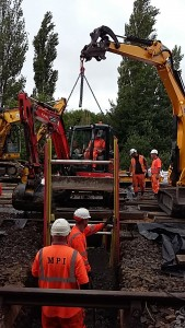 The installation of a trench box into a trench via chains and a construction vehicle on a busy work site