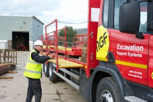 Man wearing a hardhat, glasses and a high vis vest unloading a red MGF branded truck