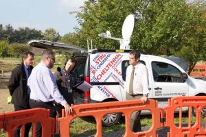 Reporters in front of a media van interviewing two men on a work site in business clothes