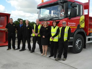 MGF personnel stood smiling in front of a red branded MGF truck