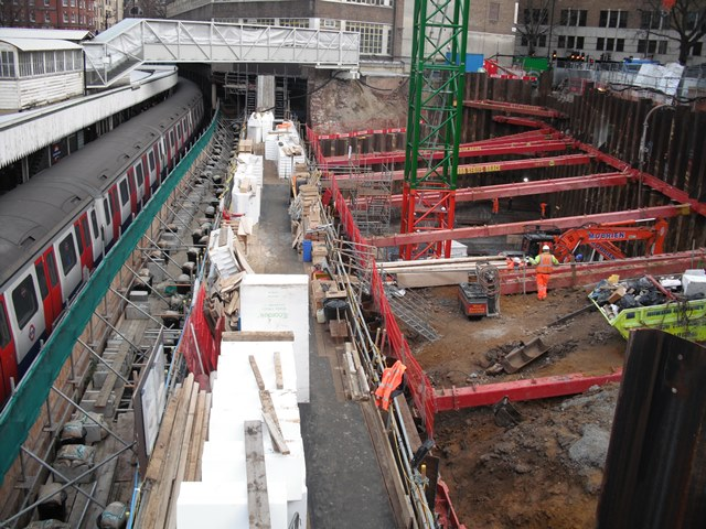 Footage of excavation fitted with red MGF temporary works next to London Underground train station