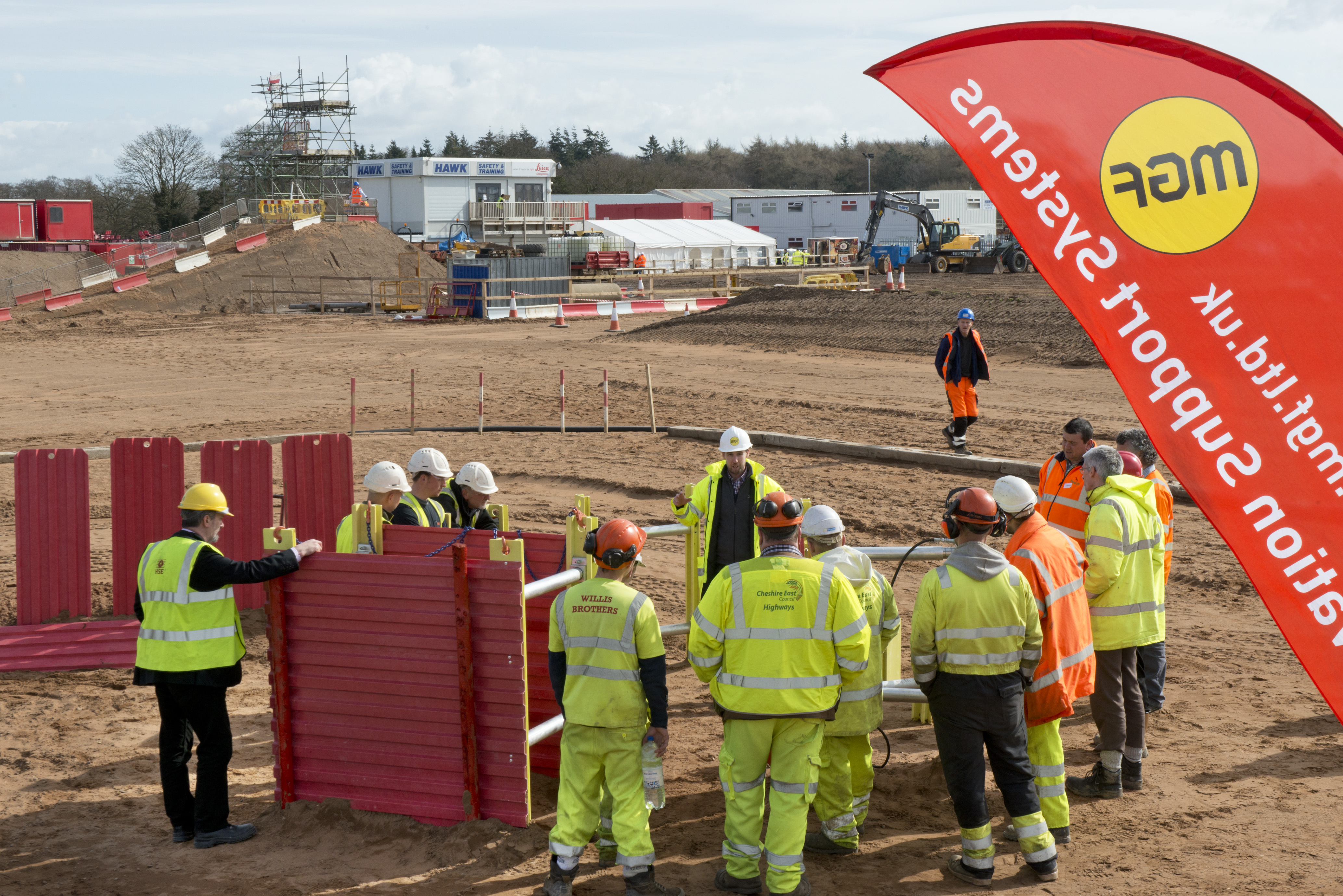 Demonstration of MGF trench box at a construction site with a group of workers in protective gear watching
