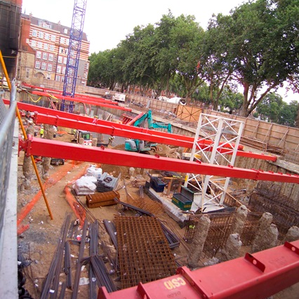 Basement excavation for a major project installed with red MGF hydraulic braces at a construction site