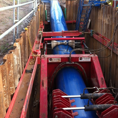Site image of red MGF equipment supporting a water pipe