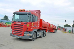 Large red MGF branded truck driving onto a yard