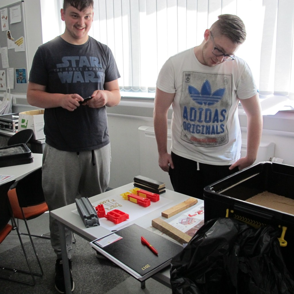 Two male students looking at miniature MGF products on a desk in an office