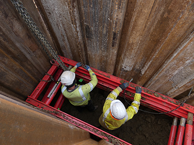 Workmen in safety gear inside a trench, secured by MGF excavation safety equipment