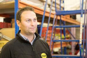 Man wearing a black MGF branded jacket inside a depot warehouse in Astley