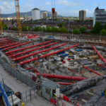 Aerial footage of large excavation with multiple red MGF hydraulic systems in place