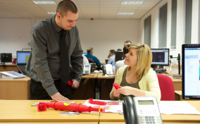A pair of male and female MGF workers at a desk speaking