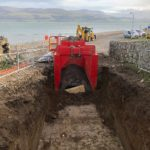 Red high clearance box fitted into the ground over a pipe next to the coast