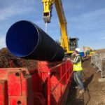 Blue pipe being lowered into a red MGF installed trench box by construction workers