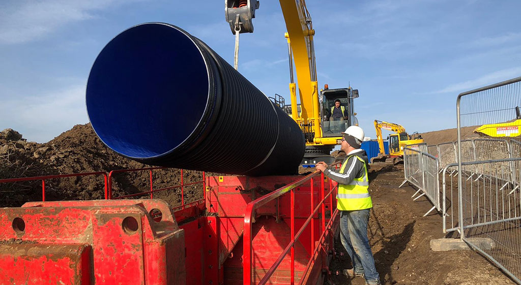 Pipe being lowered into an excavation installed with MGF kit