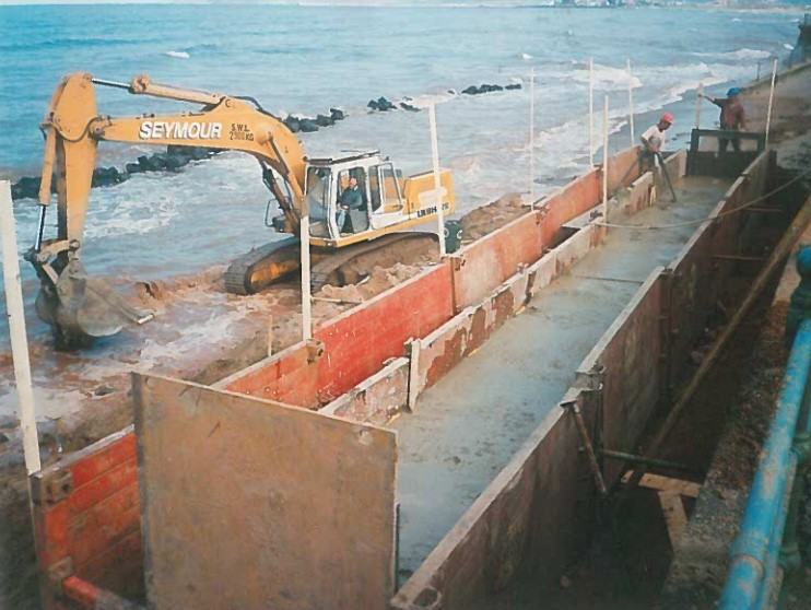 Old photo of excavator on the shore with MGF trench boxes installed